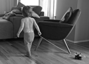 Kuvanottohetkellä lapsi on juuri toteuttanut itseään kaatamalla maitolasin paidalleen ja sen jälkeen osoittaakin vartalonhallintakykyä kiertämällä paidattomana nojatuolia ympäri samalla vetäen perässään Brio-mehiläistä.